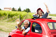 Mature couple enjoying a road trip in a small red car