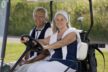 Mature couple riding in golf cart