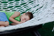 boy in a green shirt sleeping in a hammock on a large nature par