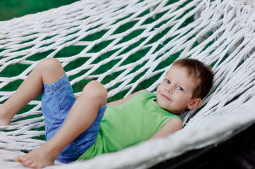 Boy in green shirt swinging in a hammock on a large nature park