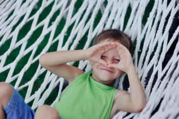 Boy in green shirt playing in a big hammock on the nature of the