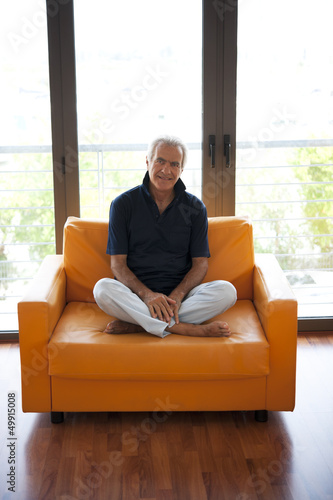 Mature man sitting in orange armchair
