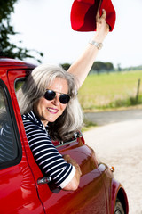 Mature woman enjoying a road trip in a small red car