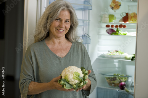 Mature woman holding cauliflower