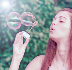 Pretty woman inflating soap-bubbles