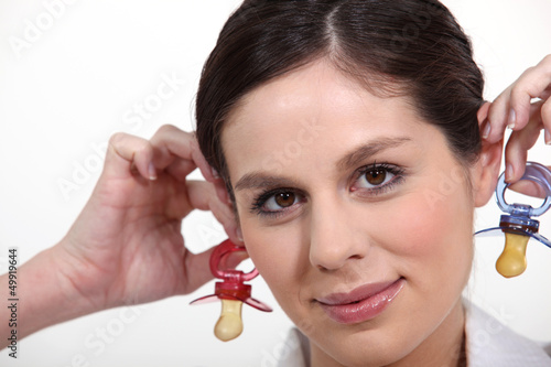 Woman holding baby soothers near her ears
