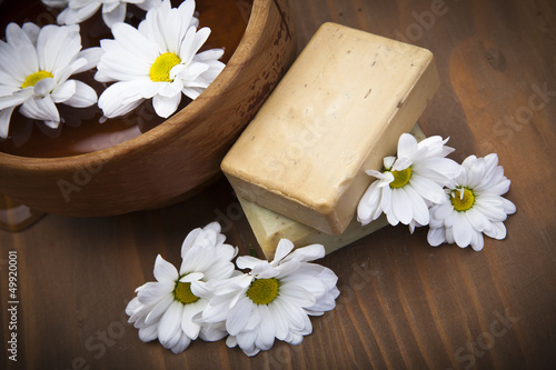 Spa soap with bowl of water and flowers