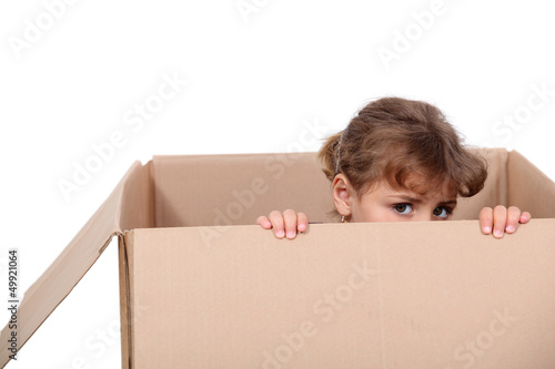 Little girl playing in a cardboard box