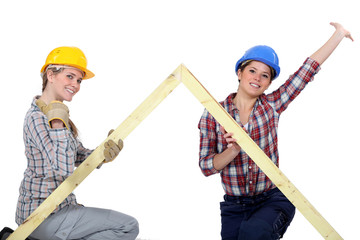 Peppy tradeswomen holding up a wooden frame