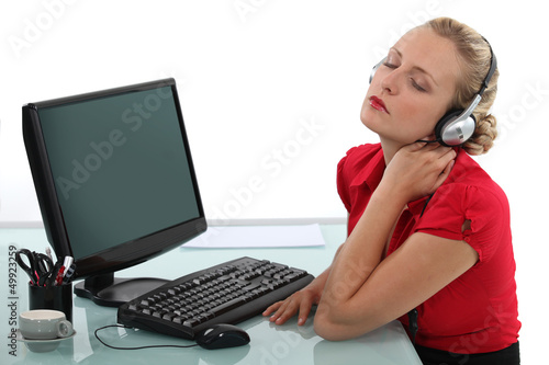 Blond office worker listening to music at desk