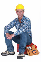 A construction worker sitting on his toolbox.