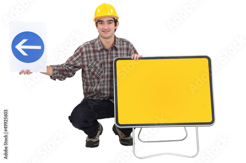 Man kneeling by two traffic signs