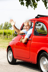 Mature man enjoying a road trip in a small red car