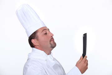 Chef looking at his reflection in a knife