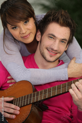 Girl hugging boy with guitar