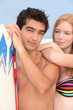 Young man and redhead with surfboard