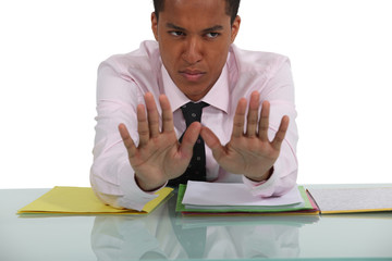 Businessman sat at desk making a stop gesture