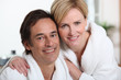 Smiling mature couple in bathrobes