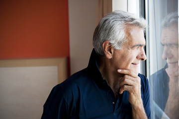 Mature man standing at window
