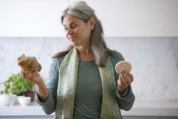 Mature woman deciding between croissant and a rice cake