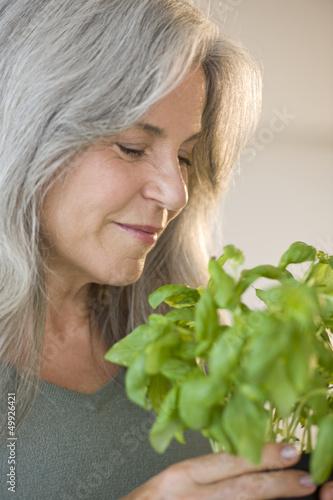 Mature woman holding basel plant