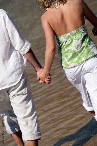 Couple holding hands while walking along the seashore