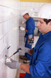 Pair of electricians wiring a white tiled room