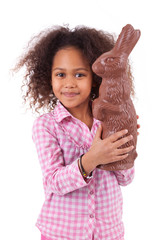 African Asian girl holding a giant chocolate rabbit