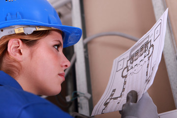 Female electrician reading diagram