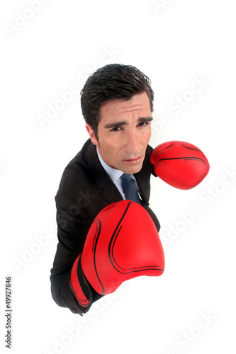 A businessman with boxing gloves on.