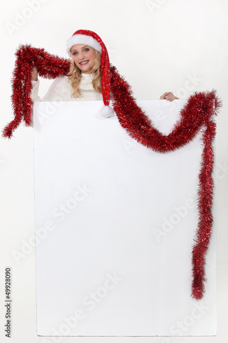 Christmassy woman with a board left blank for your message