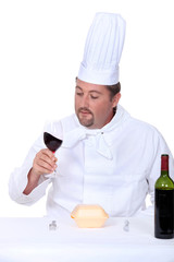 Chef with a glass of red wine and box of junk food