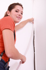 Smiling woman hiding cable on wall