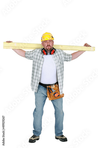 craftsman holding a wooden board on his shoulders