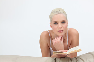 Blond woman reading in bed