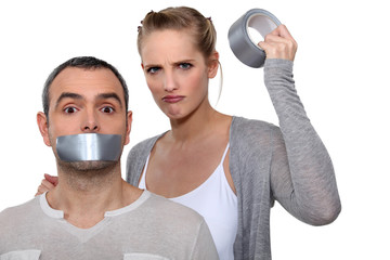 Woman taping boyfriends mouth closed