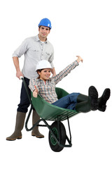Construction couple playing  with a wheelbarrow