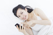 ベッドでスマートフォンを使う女性