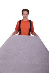 A man laying carpet.