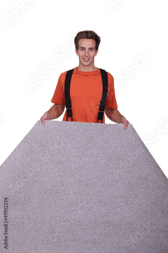 A man laying carpet.