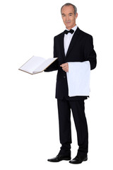 Grey haired waiter holding menu and table cloth