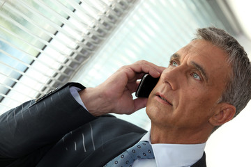 Businessman on the phone looking out of an office window