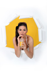 Woman busting through poster drinking orange juice