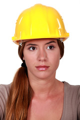 Businesswoman in a hardhat making a heart with her hands