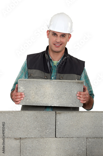 Tradesman placing a stone