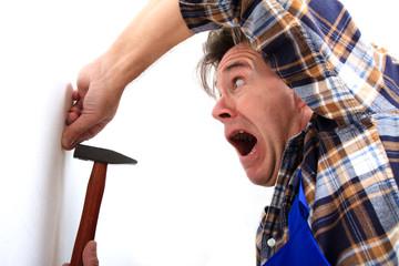 Mann haut sich mit dem Hammer auf den Finger