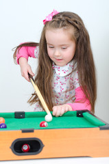 Cute little girl playing mini billiard