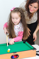 Mother teaching daughter play billiard