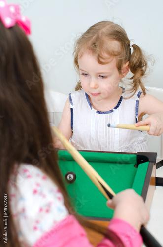 Two little girls playing mini billiard