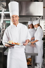 Chef Presenting Dish In Commercial Kitchen